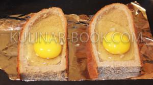 В вырезанные отверстия в хлебе вбиты яйца