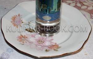 Бутылка водки стоит в центре блюда
