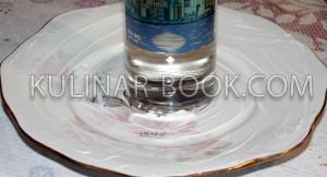 Бутылка водки стоит в центре блюда смазанного майонезом