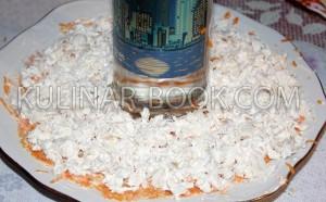 Куриная грудка выложена на блюде небольшим слоем и смазана майонезом, готовим гранатовый браслет