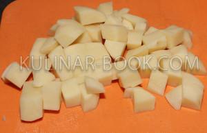Картофель нарезан кубиками  на разделочной доске